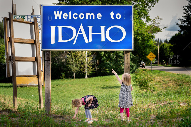 "Little girls standing by ""Welcome to Idaho"" sign"