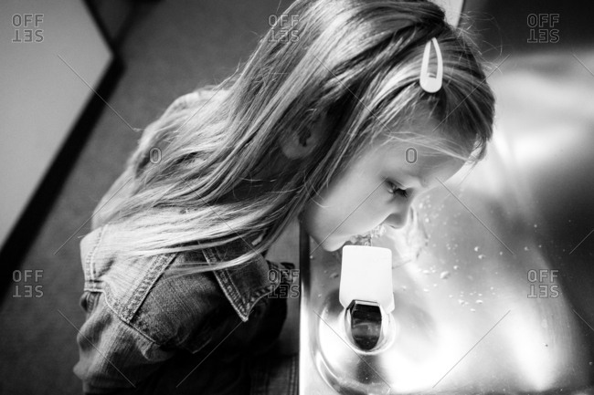 Girl drinking from water fountain in black and white