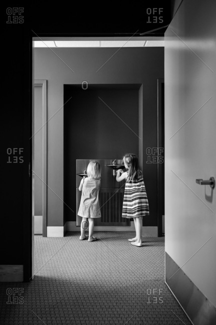 Two girls drinking from water fountain in black and white