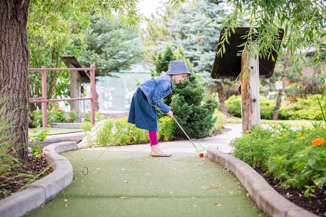 Little girl playing miniature golf