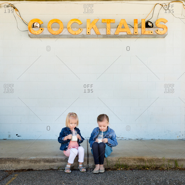 Two little girls drinking milk under cocktails sign