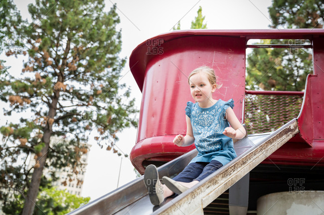 Young girl sliding down slide on a playground
