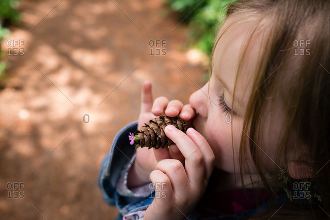 Little girl holding a pine cone with a small flower on the end