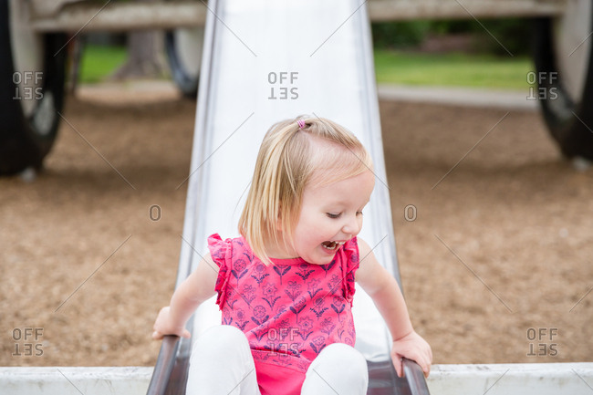 Toddler girl sliding down slide on a playground