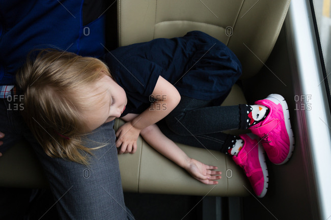 Little girl sleeping on seat and father's lap on a bus