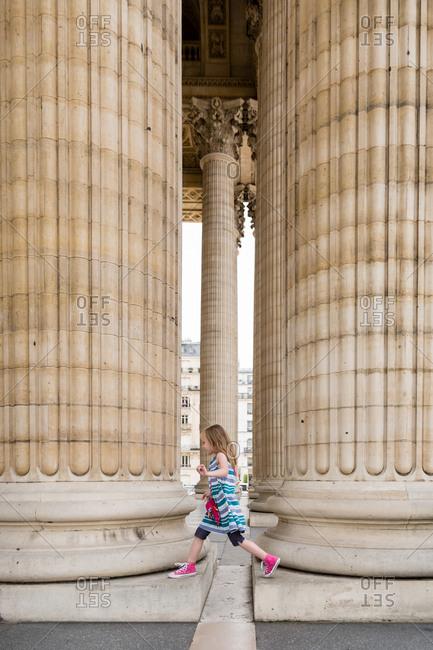 Girl stepping over gap between columns in Paris, France