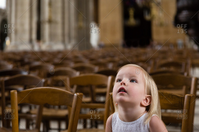 Portrait of a little blonde girl sitting on wooden chair