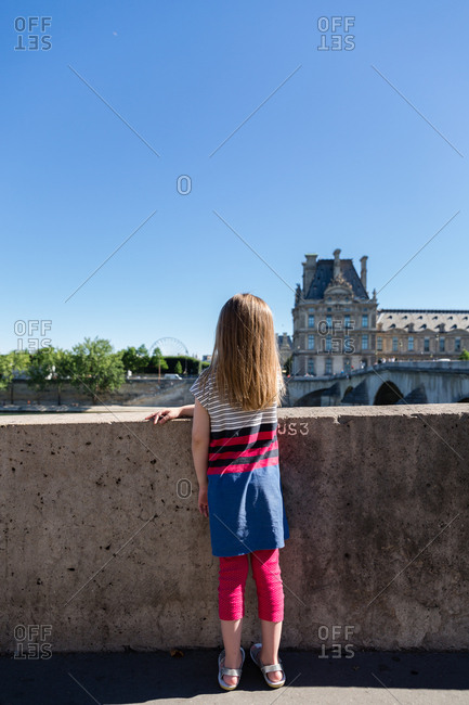 Rear view of girl looking over bridge in Paris, France