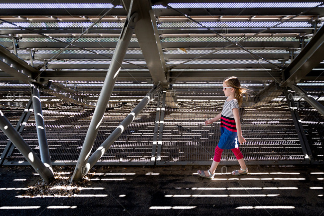 Young girl walking under bleachers