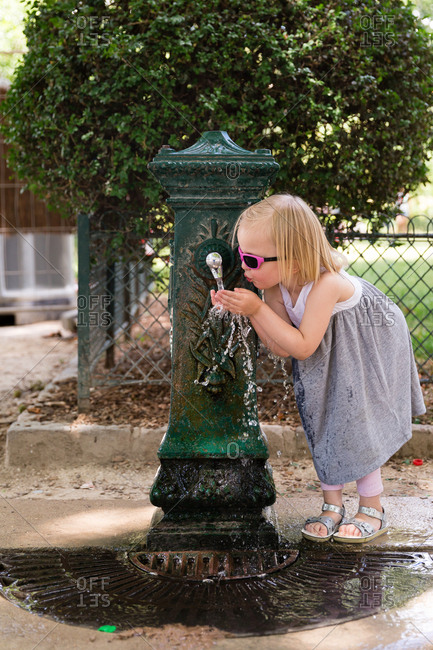 Young girl drinking from outdoor water fountain