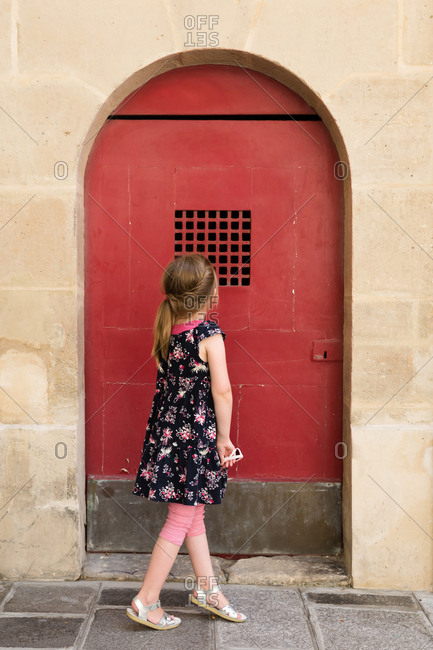 Little girl looking at a red door in Paris, France