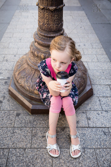 Little girl sitting and drinking to-go beverage on street in Paris, France