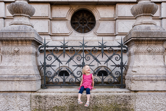 Young girl sitting by iron gate on building in Paris, France