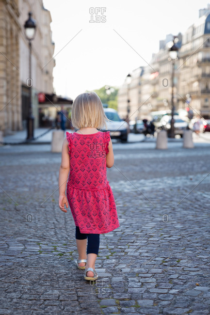 Rear view of toddler walking on cobblestone street in Paris