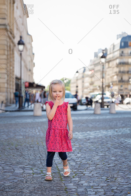 Toddler walking on cobblestone street in Paris