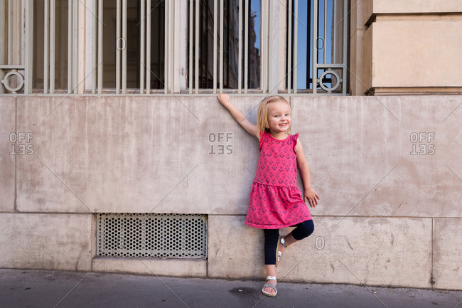 Toddler girl leaning on building in Paris, France