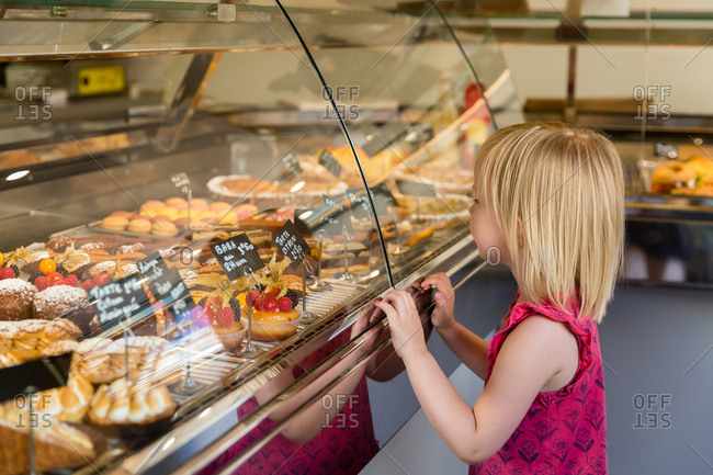 Little girl looking at sweets in a bakery
