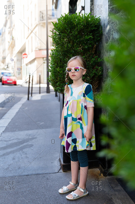 Little girl standing on sidewalk wearing sunglasses