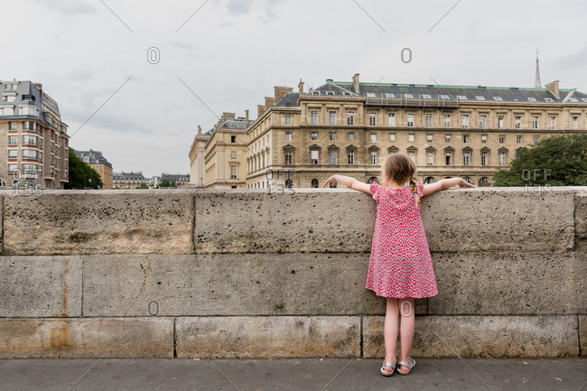Little girl looking over bridge in Paris, France