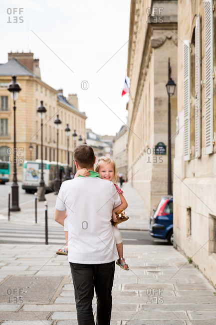 Father carrying happy toddler on streets of Paris