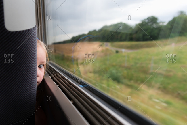 Little girl looking around seat on train