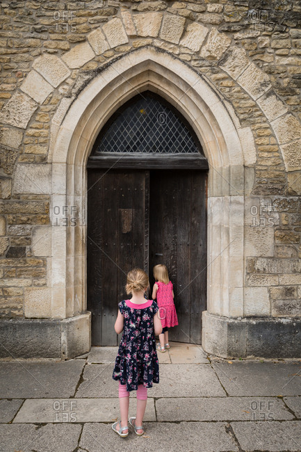 Two girls looking into old stone building with wooden door