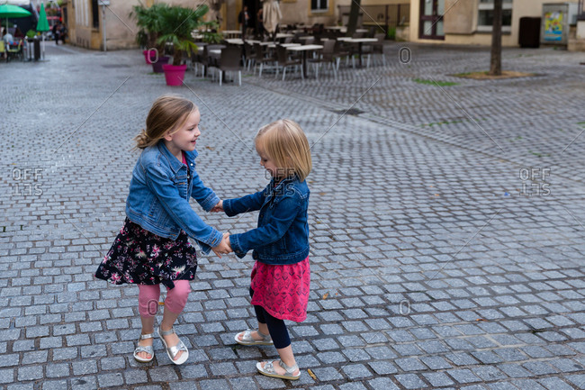 Two girls hand in hand on a cobblestone street