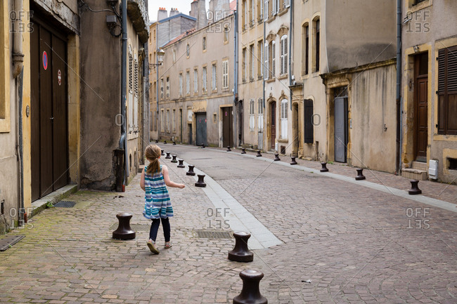 Rear view of a young girl walking down a cobblestone street
