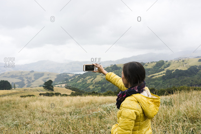 Young woman taking a cell phone photo of the New Zealand countryside