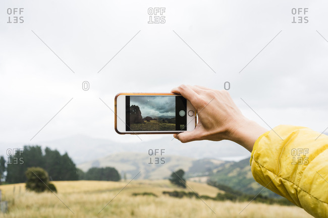 Close up of a cell phone photo being taken of the New Zealand countryside