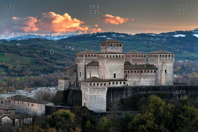 Torrechiara castle at twilight and in the background the Cusna mount, Langhirano, Emilia Romagna, Italy
