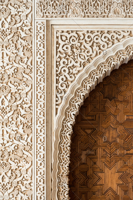 Detail of a door and wall decoration in the Arrayanes Patio, part of the Nazaries Palace, in the Alhambra complex, Granada, Spain