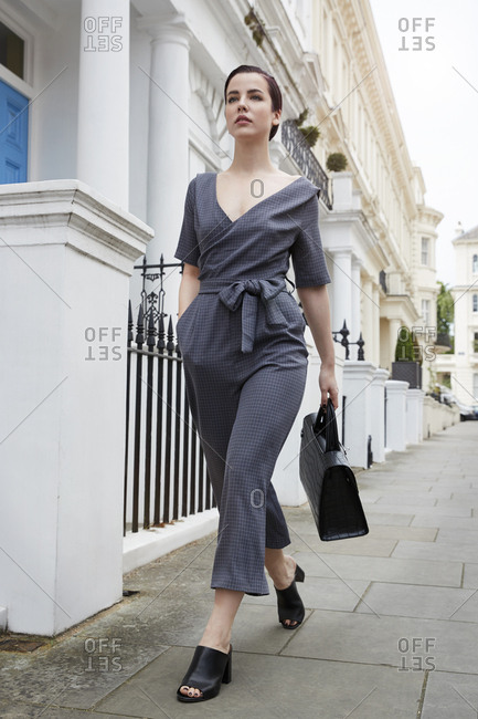 Chic businesswoman in jumpsuit walking in street, low angle