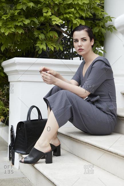 Chic woman in jumpsuit sitting on doorstep in London street