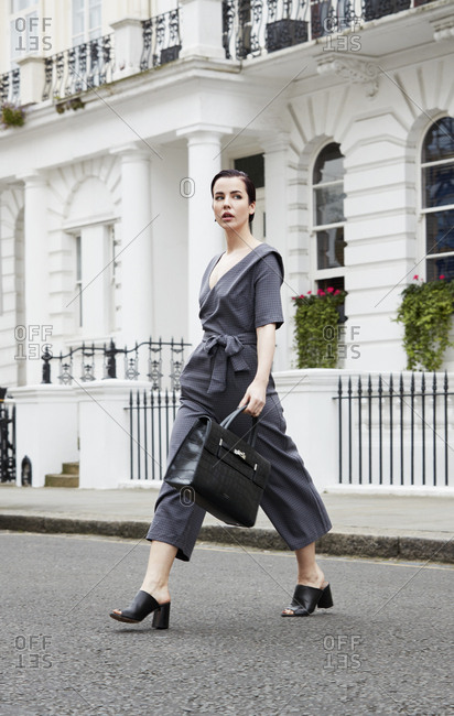 Chic young woman in grey jumpsuit crossing London street