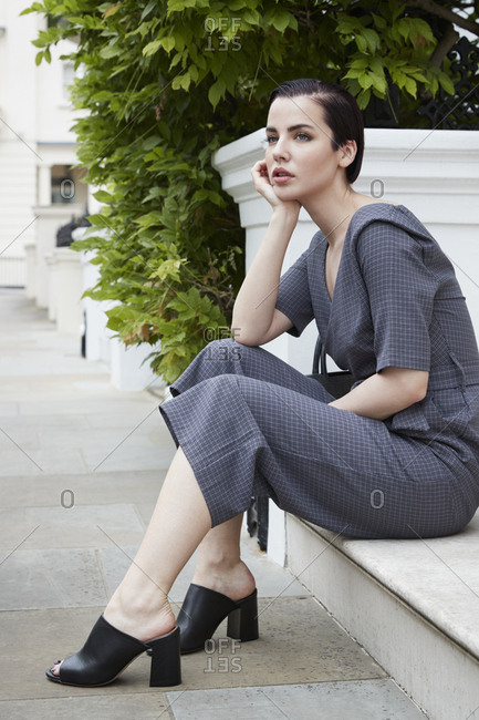 Chic woman in jumpsuit waiting on doorstep in London street