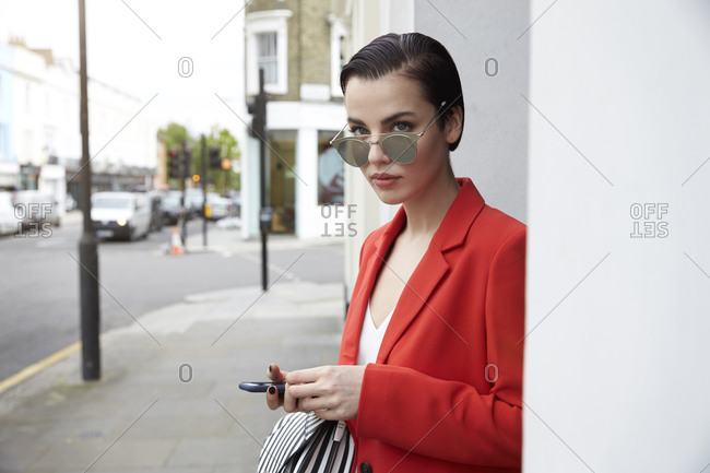 Woman in red jacket on the street, looking over sunglasses