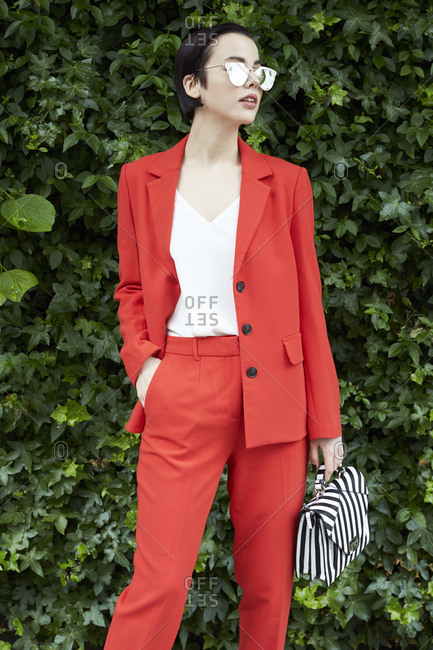 Chic woman in red suit in front of foliage looking away