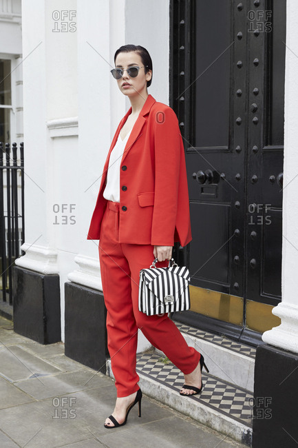 Chic young woman in red suit leaving smart London house