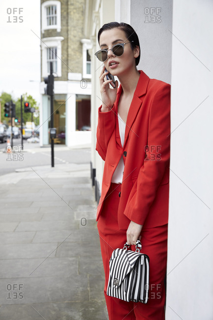Chic woman in red suit using phone in the street