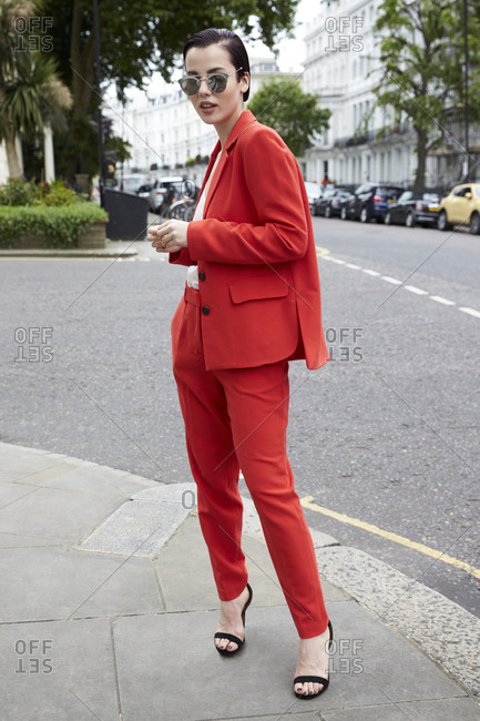 Chic woman in red suit on London street corner, full length