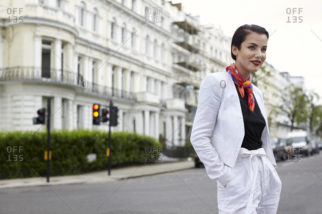 Smiling woman standing in street wearing white linen suit
