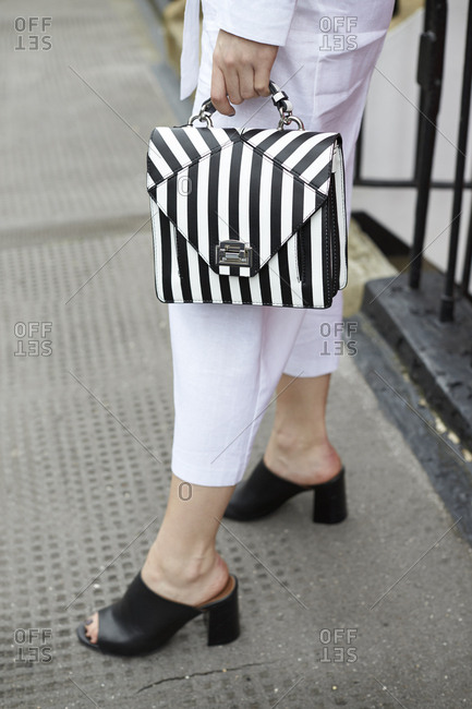 Woman in white culottes holding striped handbag, low section