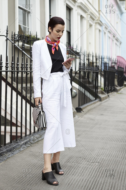 Woman in linen suit looking at phone in street, full length