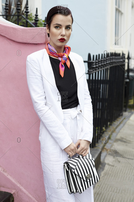 Women in white suit leaning against pink wall in street