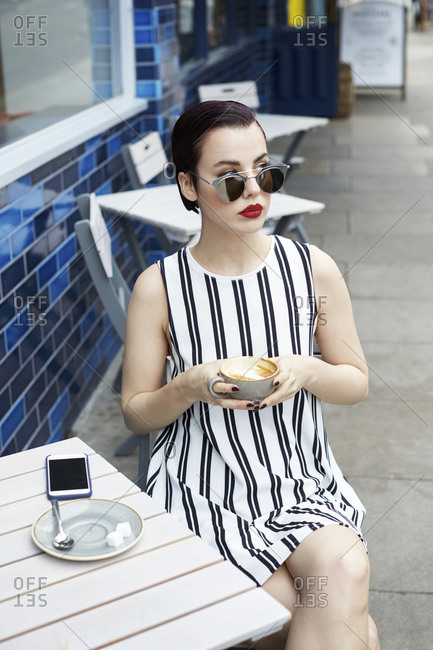 Woman in striped minidress outside a cafe looking away