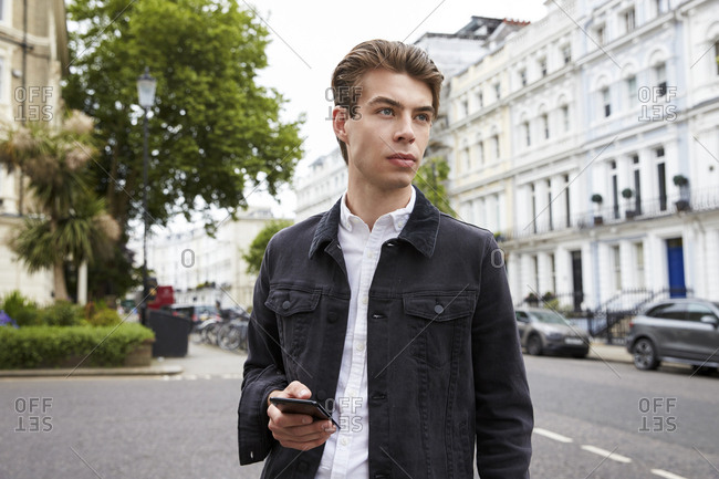 Young man standing in street holding smartphone looking away