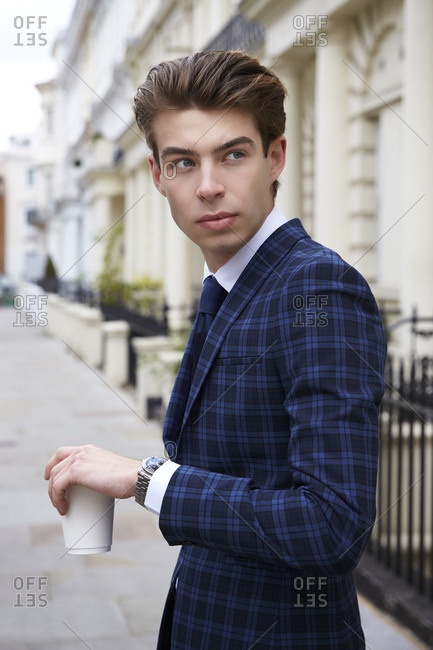 Young man in blue check suit in street with coffee, close up