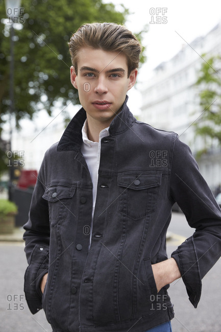 Young man in black denim jacket with hands in pockets