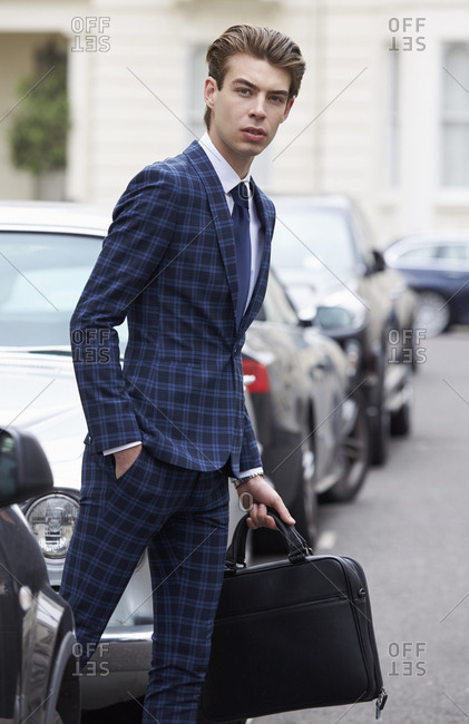 Young man in blue checked suit about to cross the street